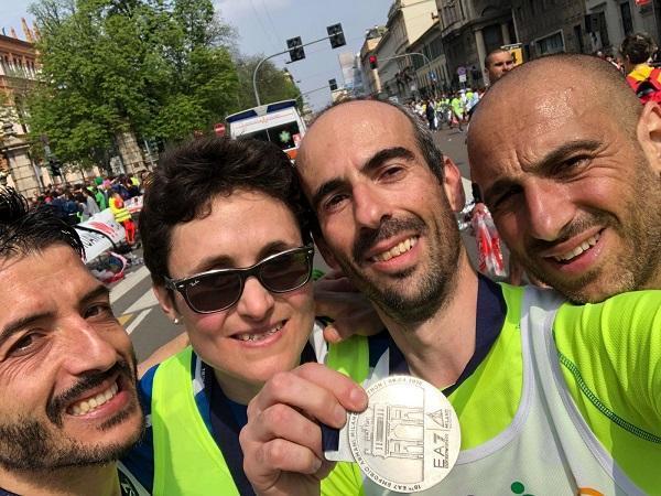 Giangavino Buseddu, Matteo Plaisant, Chiara Pandolfi e Fabio Orrù fotografati con la medaglia al traguardo della Milano Marathon