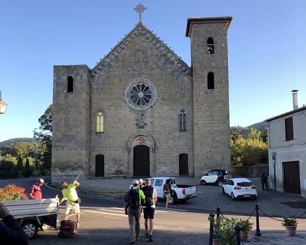si parte: sullo sfondo la chiesa di Bolsena e il gruppo che inizia il cammino